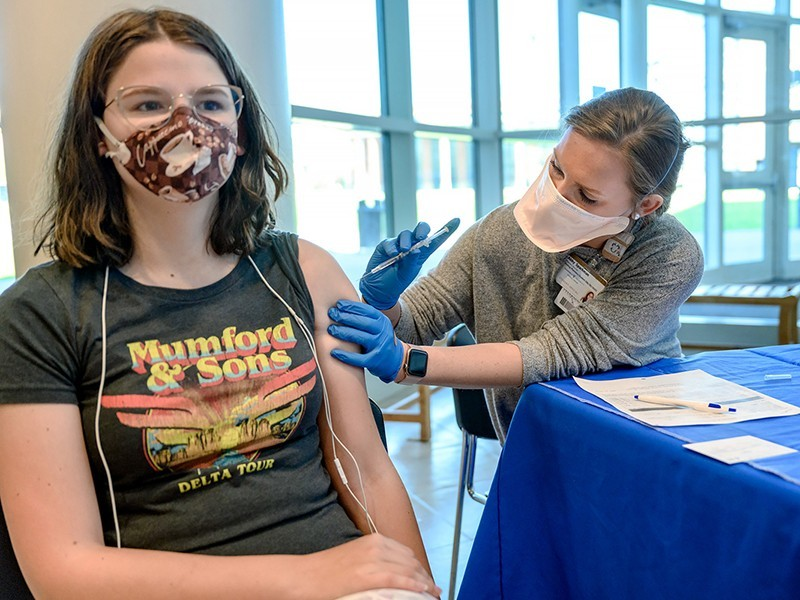 MTSU student Megan Young, left, receives the COVID-19 vaccine from Abby Sparkman of Murfreesboro, a fourth-year Lipscomb University pharmacy student, in the Health, Wellness and Recreation Ce