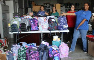 Child Advocacy Center Drug Endangered Children Coordinator Tara Davis, right, showcases the backpacks and school supplies donated to needy children. Accepting the backpacks for the CAC is Jes